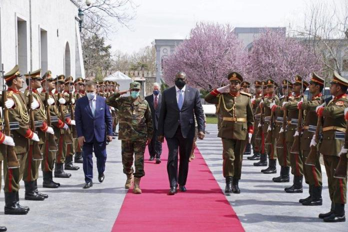 A group of people in military uniforms walking on a red carpet  Description automatically generated with medium confidence
