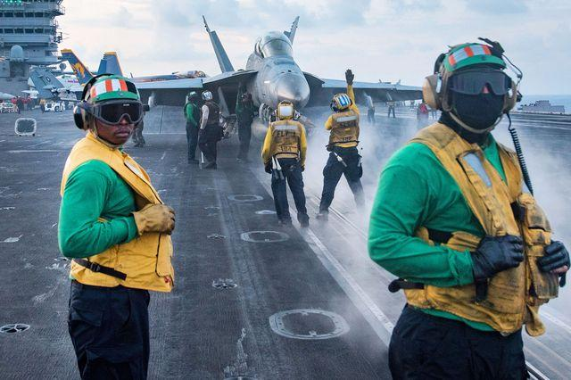 U.S. sailors conduct flight operations on the deck of the aircraft carrier USS Carl Vinson. American Navy aircraft carrier strike groups regularly patrol regional waters, fueling tensions in the South China Sea.