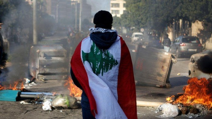 A Lebanese anti-government protester, wrapped in a national flag, stands in front of a road blocked with burning tyres and overturned rubbish bins (14 January 2020)