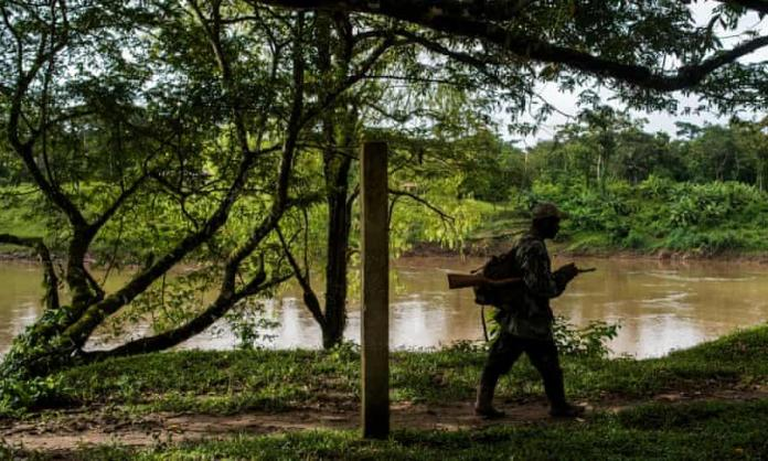 An armed Miskito man on patrol along the bank of the Coco river in Wiwinak, Nicaragua