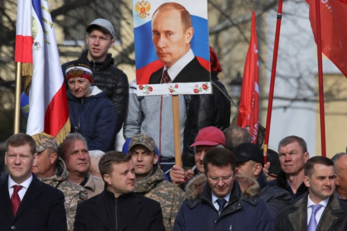 A man holds a portrait of Vladimir Putin during celebrations of the fifth anniversary of Russia's annexation of Crimea in Simferopol, Crimea March 15, 2019 [Alexey Pavlishak/Reuters]