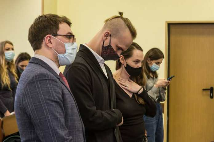 Standing among a row of people wearing face masks in a courtroom, Lang looks to the ground and Ospiovich puts a hand to her neck