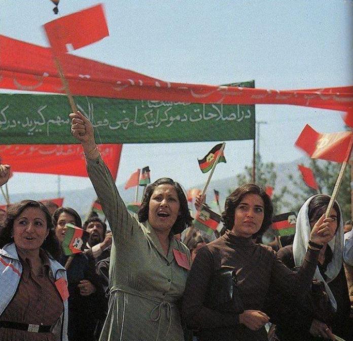 Un grupo de personas sosteniendo una bandera Descripción generada automáticamente con poca confianza
