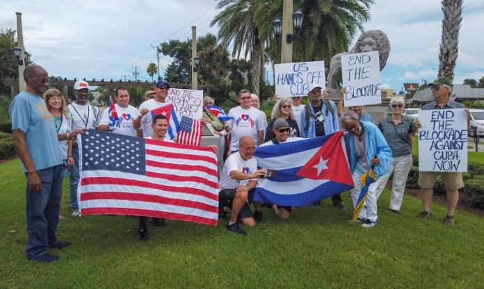 Un grupo de personas sosteniendo una bandera Descripción generada automáticamente con una confianza media