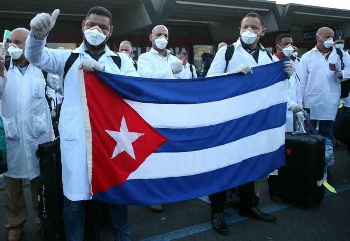 Un grupo de personas con máscaras blancas sosteniendo una bandera Descripción generada automáticamente con poca confianza