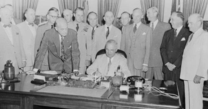Un grupo de hombres de pie alrededor de una mesa Descripción generada automáticamente con una confianza media