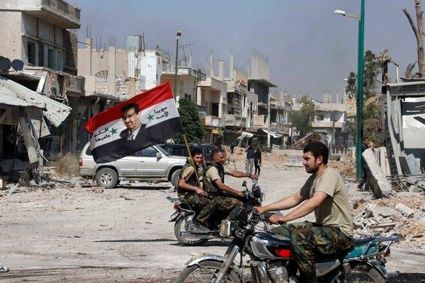 Forces loyal to President Bashar al-Assad carried a flag on Wednesday after taking the town of Qusayr.