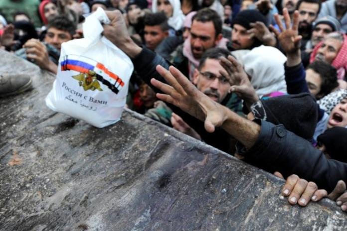 Syrians who fled east Aleppo reach for Russian aid in the government-controlled area of Jibreen [AP]