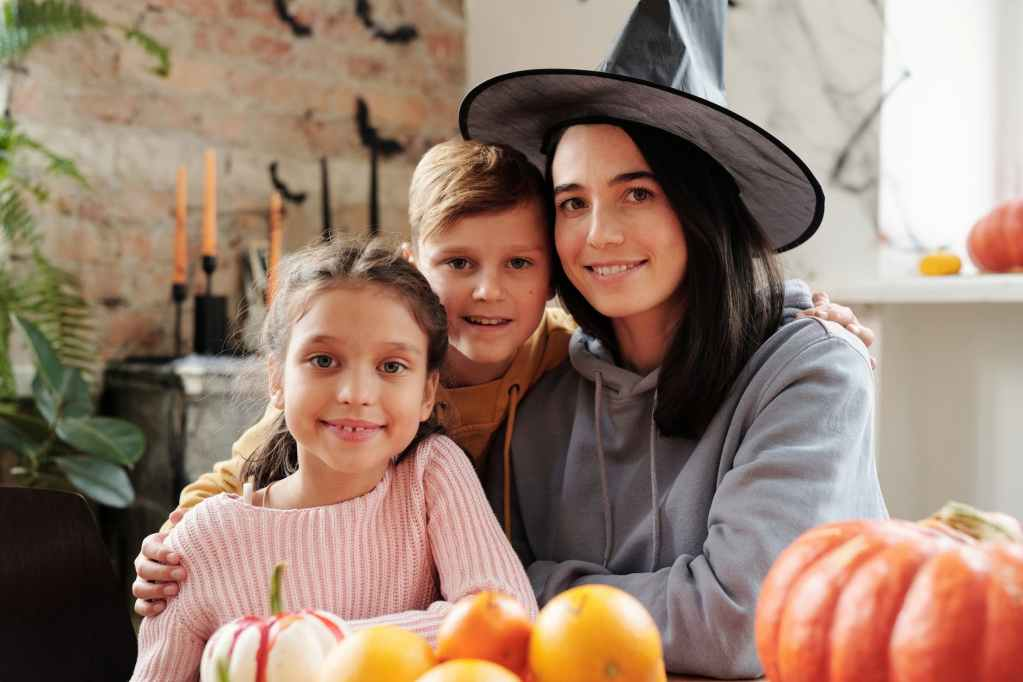 mother wearing a witch hat and posing with her children