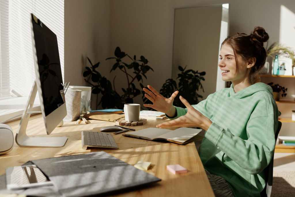 woman in green and white stripe shirt sitting at table