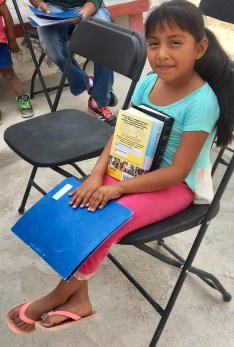 Evelin loves her Bible and loves to sing songs from the blue folder with us!