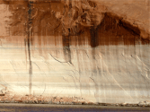 Water experts say that if the ongoing drought persists, Lake Powell could be empty within three years, and call could be placed on the upper basin to curtail water rights. To avoid the chaos such an unprecedented call might bring, state officials are discussing how a more orderly, but still mandatory curtailment of water uses, might need to be implemented. A wall bleached, and stained, in Lake Powell. Photo credit Brent Gardner-Smith @AspenJournalism.