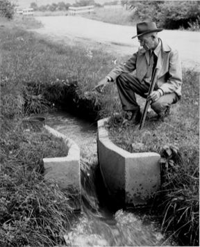 Ralph Parshall squats next to the flume he designed at the Bellevue Hydrology Lab using water from the Cache la Poudre River. 1946. Photo Credit: Water Resource Archive, Colorado State University, via Legacy Water News.