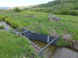 This recently installed Parshall flume in the Yampa River basin replaced the old, rusty device in the background. Division 6 engineer Erin Light is granting extensions to water users who work with her office to meet a requirement for measuring devices. Photo credit: Aspen Journalism/Heather Sackett