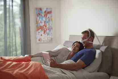 Man Reading in Bed with CPAP Nasal Mask
