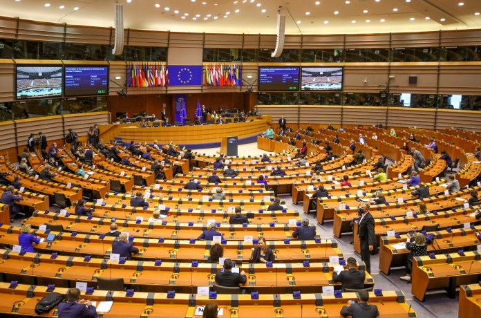 Lawmakers are shown seated at desks in rows facing a podium and EU flags in a large parliamentary building.