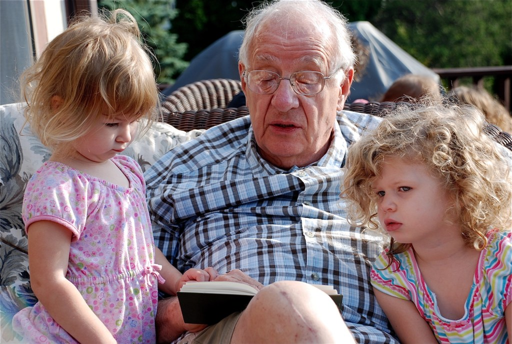 Ted Loder reading a book to Hannah (3), who is looking skeptical and Chloe (4), who is imagining the story.