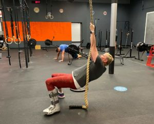 CPM member, Crash, doing a rope climb in the gym
