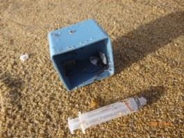 Seringues sur la plage et pouces-pieds colonisant les déchets