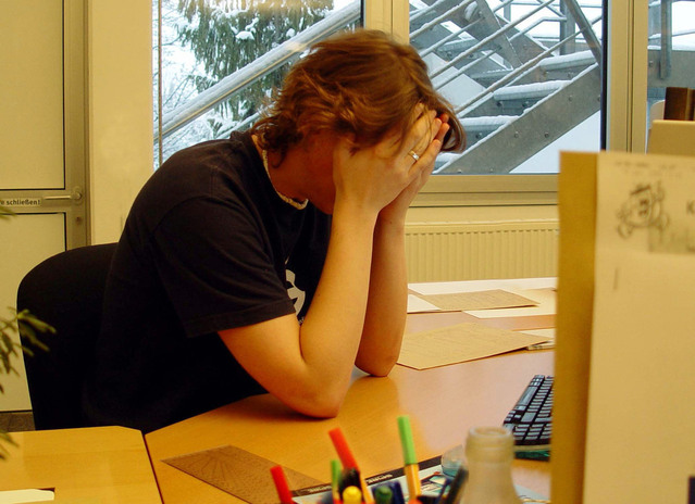 Image of person holding head in their hands at a desk