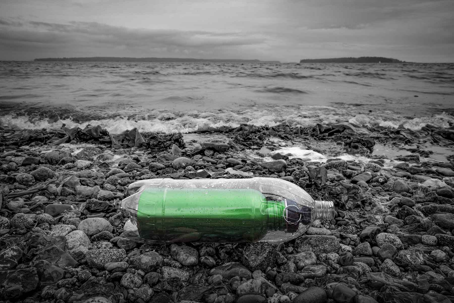 A green refillable bottle rests inside a plastic bottle