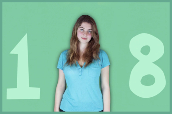 Image of girl with long brown hair, wearing a blue t-shirt, standing in front of a turqoise background with the number 18 written on it