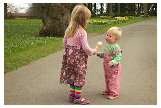 A young girl 'interviews' her younger brother with an ice cream microphone. Bucolic background with flowers. CRAE logo on right. Image by Richard Leeming , c/o Flickr. CC BY-SA 2.0