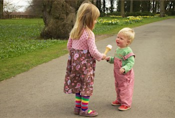 A young girl 'interviews' her younger brother with an ice cream microphone. Bucolic background with flowers. Image by Richard Leeming , c/o Flickr. CC BY-SA 2.0
