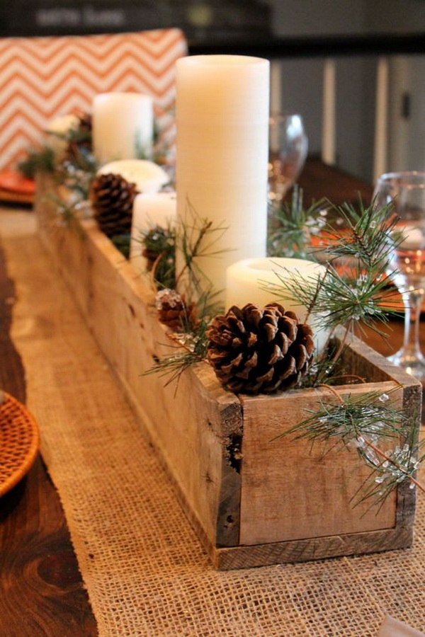 Rustic pallet wood centerpiece box with pine cones, candles and cedar.