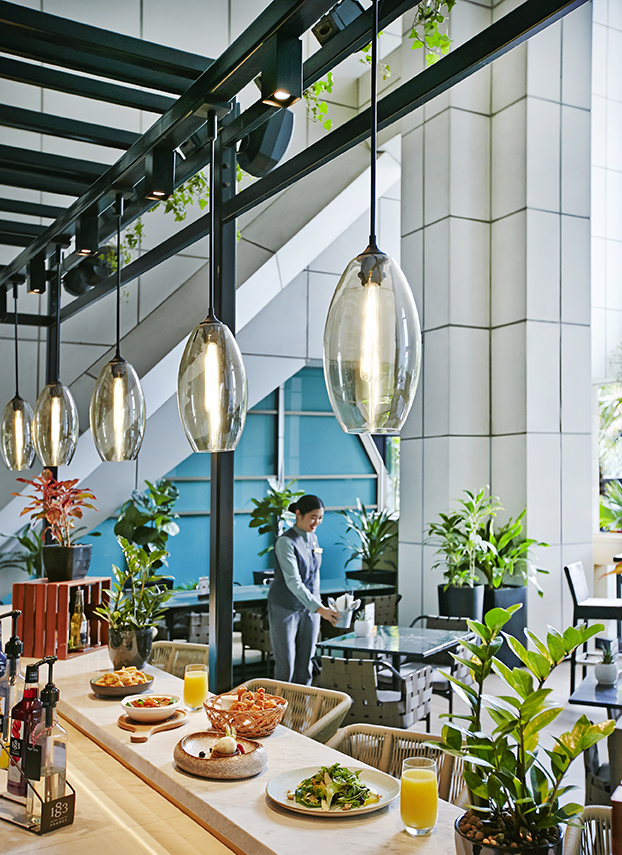 Digital Agency Case Study - Orchard Hotel Singapore - Al Fresco dining at The Orchard Cafe; waitress and food and orange juice on bar; potted plants with ample seating space