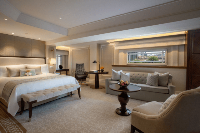 The Fullerton Hotel Singapore's Heritage King Room with plush bed, sofa and window; good for staycation