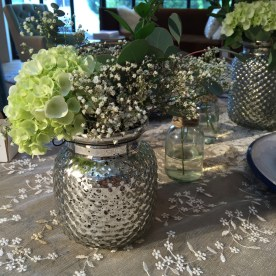 A beautiful tablescape. Wood table, lace cloth, simple vases with babies breath and hydrangeas.