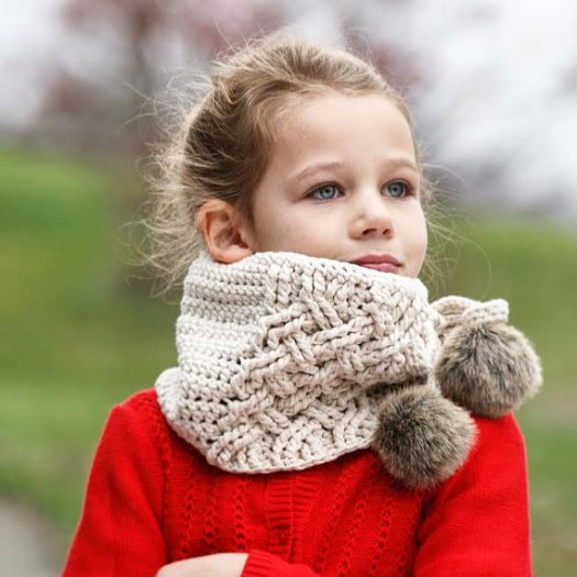I love the cable-knit look of this crocheted scarf pattern... and the adorable pompoms make it so unique! What a cozy looking cowl crochet pattern!