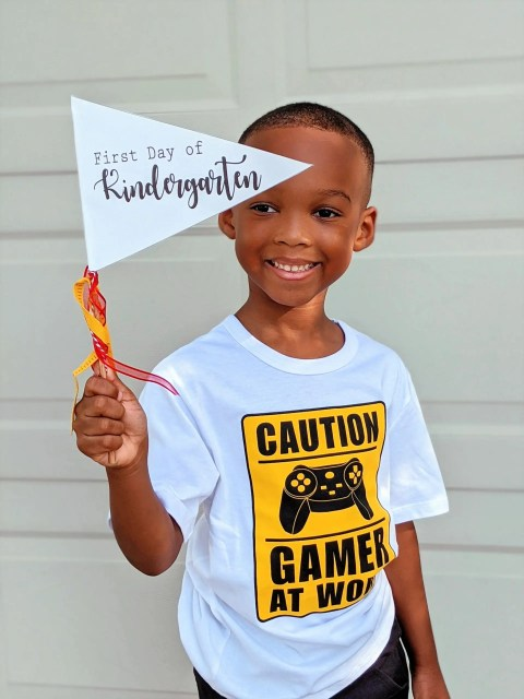 Kindergarten student holding a pennant for back to school pictures.