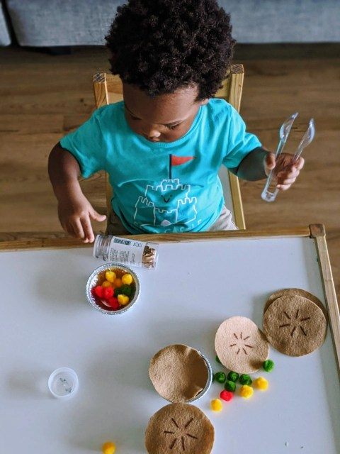 Black toddler playing with homemade apple pie toy set