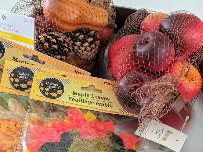 supplies for fall activity for kids including apples, pumpkins and fake leaves