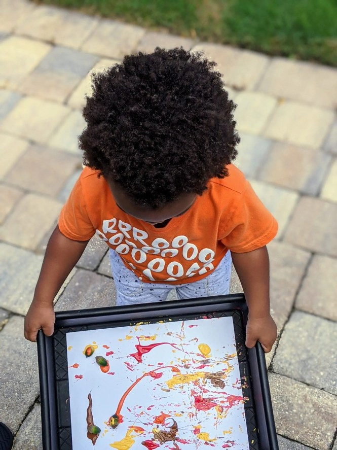 toddler with acorn art project
