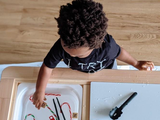 toddler playing at sensory table