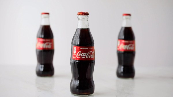 three coca cola bottles isolated on gray background