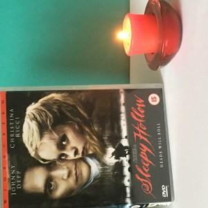 Autumn Movie Favourites - Sleepy Hollow DVD and burning red candle in red glass holder