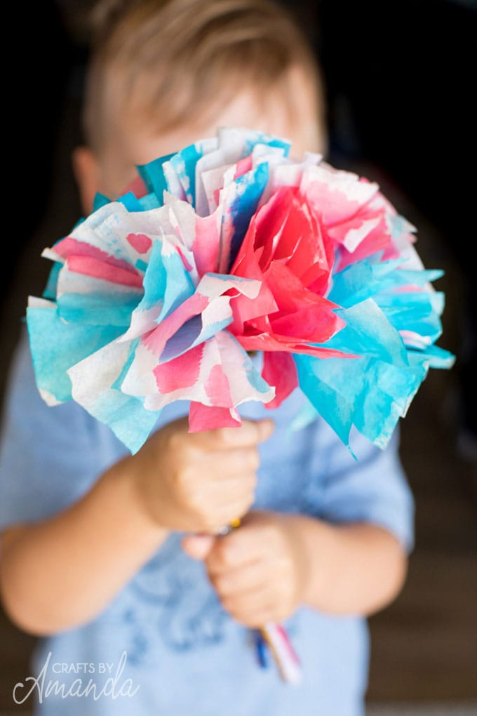 little boy holding a boquet of flowers made from watercolors and coffee filters