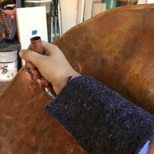 The hand of Athena, aka Lilah Lloyd, holding a DIY copper shield that is Pythagorean orders cooler than any other shield in Halloween history.