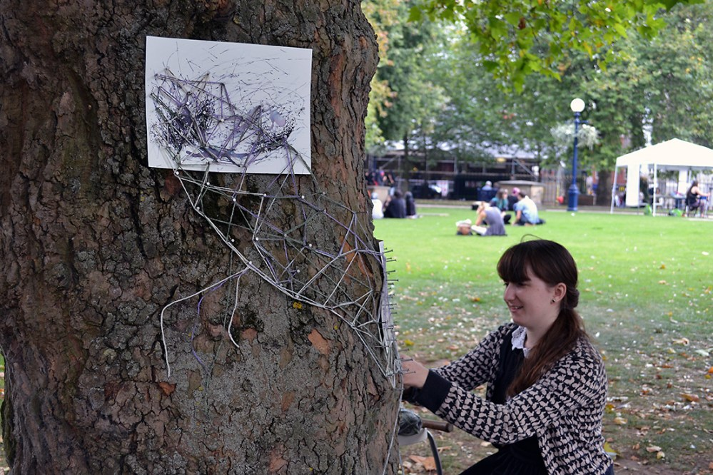 The artist places string around the pins placed on the tree. Ink drawings are placed underneath these.