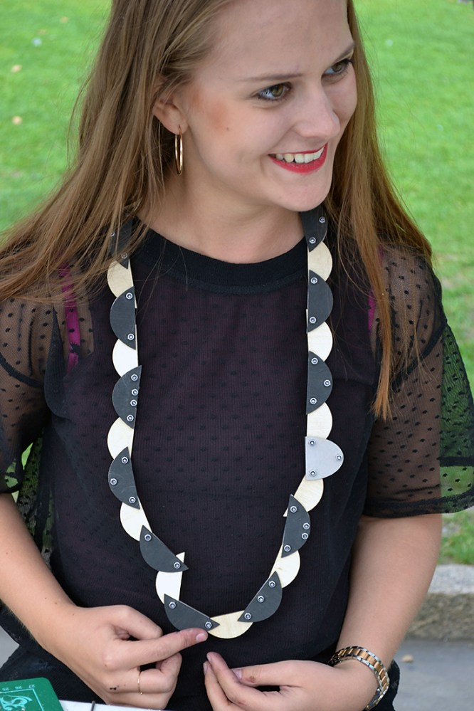 A woman with a long black and white necklace, made of semi circles and bolted together, around her neck smiles.