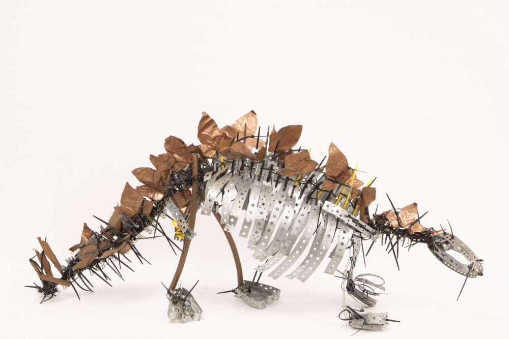 A model of a dinosaur made from pieces of metal.