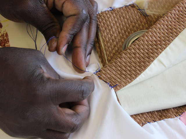 A close up of a man's hands sewing large pieces of fabric.