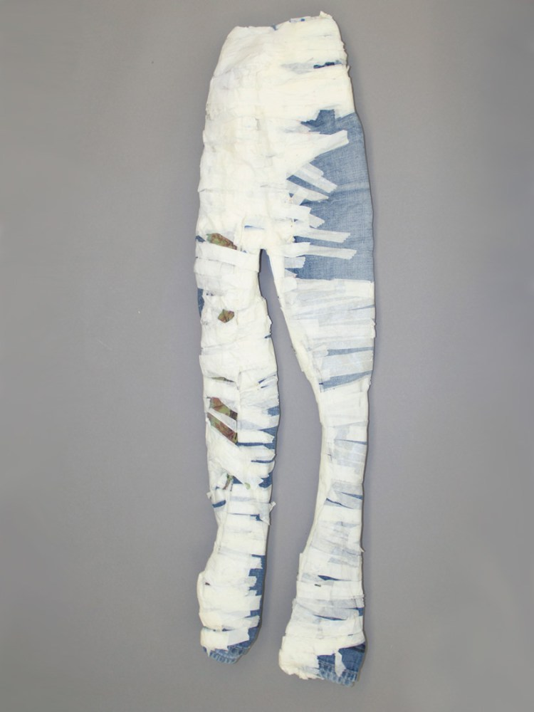 A pair of 3D jeans covered in tape sit on a wall.