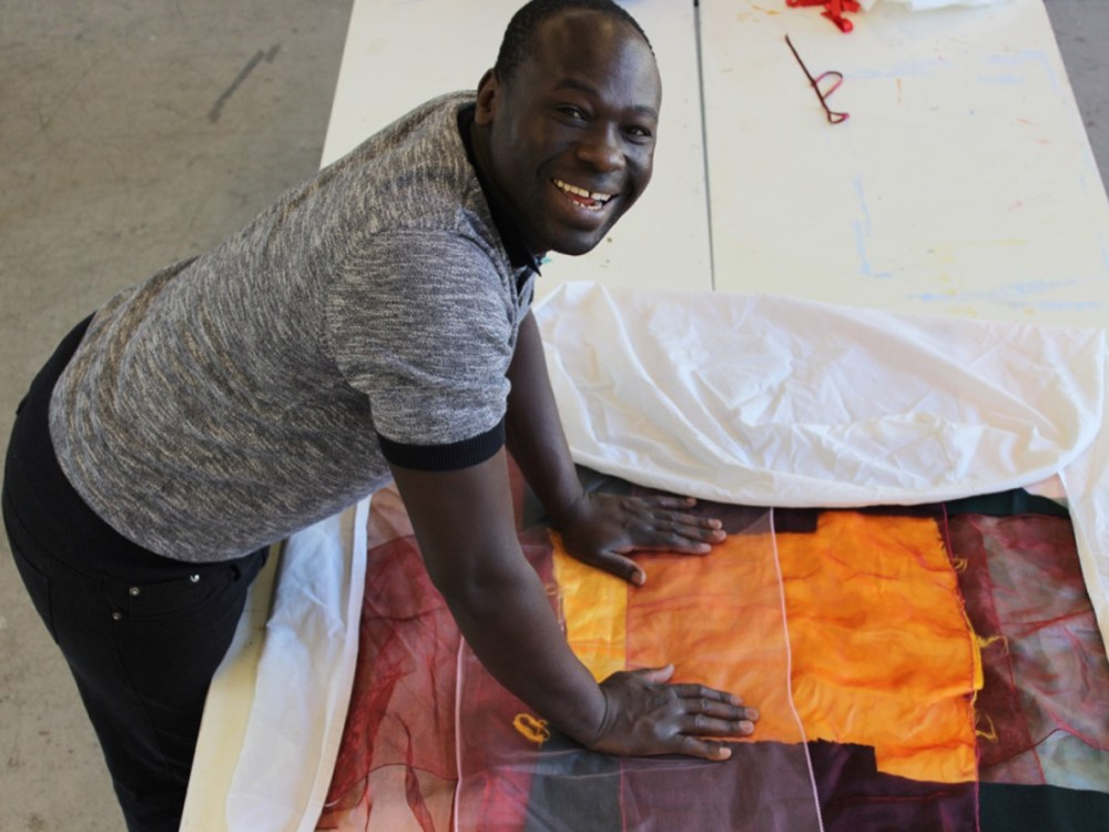 Andrew smiling whilst in the studio working on one of his textile pieces