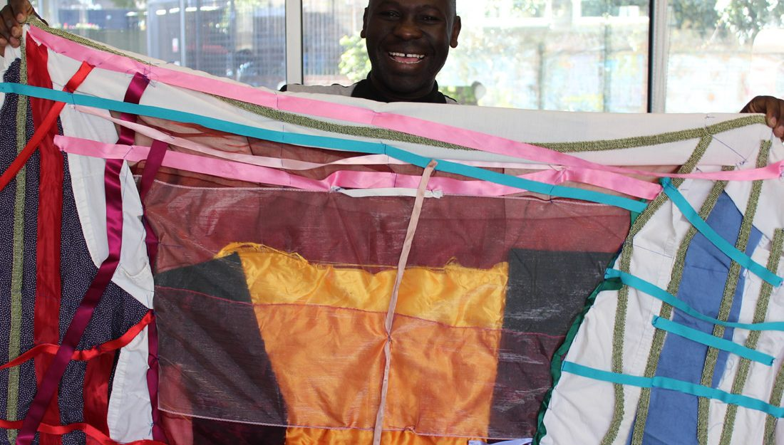 Andrew proudly smiling holding up brightly coloured textile flag he has created