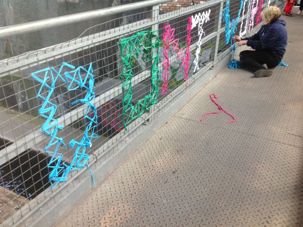 The words 'don't worry' are weaved onto a metal bridge using yarn of various colours. A lady sits and finishes weaving the letter W.